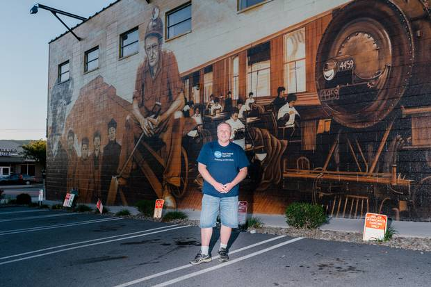 Ron Faraday, president of the Greater Pittston Historical Society and a production supervisor at Greiner Packaging, stands in front of a mural commemorating the Pennsylvania town's history.