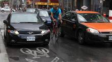 A cyclist passes a car parked in ta bike lane on Wellesley Street in downtown Toronto in 2011. (Deborah Baic/The Globe and Mail)
