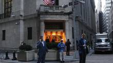 Traders stand outside the New York Stock Exchange prior to the opening bell October 31, 2012. (BRENDAN MCDERMID/REUTERS)