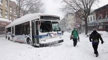 People pass a city bus stuck in the snow, Monday, Dec. 27, 2010 in the Brooklyn borough of New York. A powerful East Coast blizzard menaced would be travelers Monday. Two buses and two sanitation trucks were stuck on the same block in the Park Slope neighborhood of Brooklyn. (Mark Lennihan)