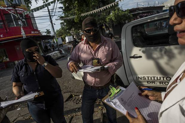 Investigators process the crime scene of a man shot to death in downtown San Salvador, El Salvador, May 29, 2015.