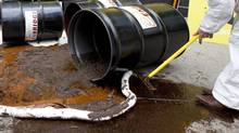 A member of Greenpeace cleans up a mock oil spill outside the Enbridge Northern Gateway pipeline office in downtown Vancouver, Wednesday, June 13, 2012. (JONATHAN HAYWARD/THE CANADIAN PRESS)