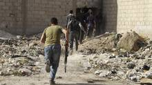 Free Syrian Army fighters carry their weapons as their move towards their positions in the al-Ziyabiya area in Damascus May 5, 2013. (STRINGER/REUTERS)