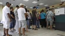People line up inside an unemployment bureau in Athens Sept. 6, 2012. Greece's jobless rate scaled a new record high of 24.4 per cent in June from an upwardly revised 23.5 per cent in May. (JOHN KOLESIDIS/REUTERS)