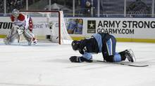 In this Jan. 1, 2011, photo, Pittsburgh Penguins' Sidney Crosby, right, crawls on the ice after being injured in the second period of the Winter Classic in Pittsburgh. (Keith Srakocic/The Associated Press)