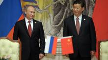 Russia's President Vladimir Putin and China's President Xi Jinping, right, smile during signing ceremony in Shanghai. China signed a long-awaited, 30-year deal to buy Russian natural gas worth some $400-billion. (ALEXEI DRUZHININ/AP)
