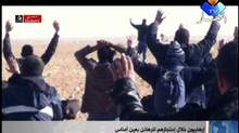 "In this image made from video, a group of people believed to be hostages kneel in the sand with their hands in the air at an unknown location in Algeria. An Algerian security official says de-mining squads searching for explosives found ""numerous"" bodies Sunday, Jan. 20, 2012 at a gas refinery where Islamic militants took dozens of foreign workers hostage. (Ennahar TV/AP)"