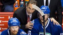 Vancouver Canucks' head coach John Tortorella, centre, talks to Nicklas Jensen, right, after the team gave up a goal to the Anahe