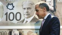 Bank of Canada Governor Mark Carney walks past a poster of the bank's new circulating $100 bill, Canada's first polymer bank note, in Toronto on Nov. 14, 2011. (Nathan Denette/The Canadian Press/Nathan Denette/The Canadian Press)