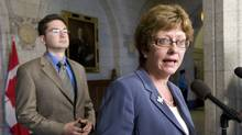 Minister of Human Resources and Skills Development Diane Finley speaks with the media about the EI working group as fellow committee member Pierre Poilievre looks on during an availability outside the House of Commons on Parliament Hill on Thursday. (Adrian Wyld)