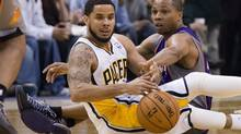 Indiana Pacers' D.J. Augustin, left, and Phoenix Suns' Sebastian Telfair go after a loose ball on the floor during the second half of an NBA basketball game in Indianapolis on Dec. 28, 2012. (Doug McSchooler/AP)
