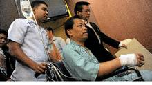 Thai opposition politician Pracha Prasopdee, centre, leaves in a wheelchair after addressing a press conference at a hospital in Bangkok on May 12, 2011, two days after he was shot in the back in the outskirts of the Thai capital. (CHRISTOPHE ARCHAMBAULT/AFP/Getty Images)