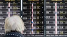 A passenger looks up at the flight status signs at Pearson Airport in Toronto on Jan. 8, 2013, showing many cancellations and delays. (Deborah Baic/The Globe and Mail)