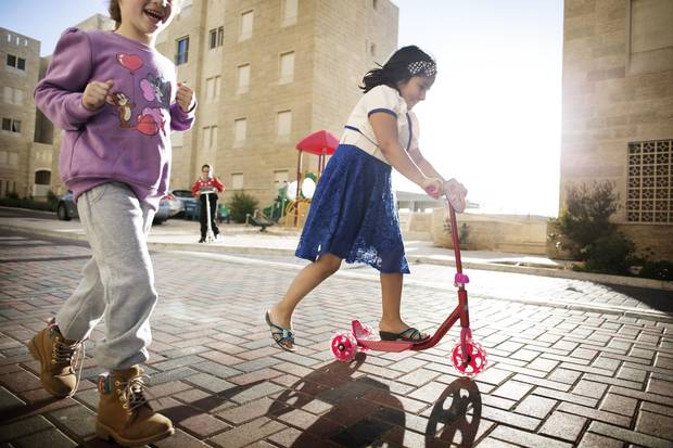 Young Nour Salameh, right, joins neighbourhood friends in making good use of the communal play area.