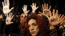 "Anti-bailout protesters raise their open palms showing the word ""No"" after Cyprus's parliament rejected a proposed levy on bank deposits in Nicosia March 19, 2013. Cyprus's parliament overwhelmingly rejected a proposed levy on bank deposits as a condition for a European bailout on Tuesday, throwing euro zone efforts to rescue the latest casualty of the currency area's debt crisis into disarray. (YORGOS KARAHALIS/REUTERS)"