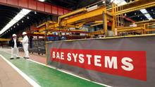 Workmen stand at the BAE Systems' Govan shipyard in Glasgow, Scotland, in this file picture taken May 26, 2011. (DAVID MOIR/REUTERS)