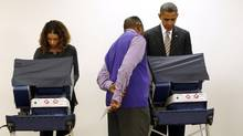 U.S. President Barack Obama is assisted as he casts his vote early at the Martin Luther King Community Center in Chicago on Oct. 25. It was the first time a U.S. president had cast his vote early. Scenes of presidential candidates and their spouses voting on Election Day are typically a ritual that ends a long campaign season. (KEVIN LAMARQUE/REUTERS)