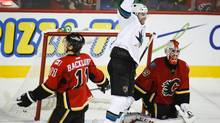 San Jose Sharks' Brad Stuart, centre, celebrates his game winning goal as Calgary Flames goalie Reto Berra, right, looks away and Mikael Backlund skates away during overtime NHL action in Calgary, Alta., Tuesday, Nov. 12, 2013. The Sharks beat the Flames 3-2 in overtime. (Jeff McIntosh/THE CANADIAN PRESS)