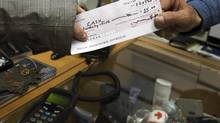 A cheque is passed Tuesday, March 22, 2011 in Montreal. (Ryan Remiorz/THE CANADIAN PRESS)