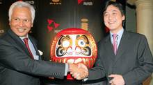 New Delhi, INDIA: Senior Vice President and Managing Director of Multimedia services at NTT DoCoMo Inc. Takeshi Natsuno (R) shakes hands with Managing Director of Hutchison Essar Mobile, Asim Ghosh in front of a Japan's Darum doll during a launch function in New Delhi, 15 December 2006. (RAVEENDRAN/AFP/Getty Images)