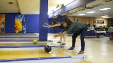 This isn't your father's alumni association meeting: Sharon Au, left, and Nina Coutinho go head to head at a University of Toronto Schools alumni bowling outing in Toronto. (Matthew Sherwood for The Globe aND MAIL)