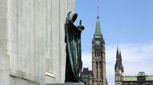 The statue of Ivstitia (Justice) on the front steps of the Supreme Court of Canada is pictured against the Peace Tower of Parliament on May 22, 2014 in Ottawa. (Dave Chan For The Globe and Mail)