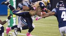 Winnipeg Blue Bombers running back Chad Simpson, centre, dives into the end zone for a touch down past Toronto Argonauts line backer Robert McCune, left, and Argonauts defensive back Pacino Horne during first half CFL action in Toronto on Friday, Oct. 19, 2012. (Nathan Denette/THE CANADIAN PRESS)