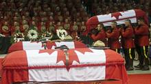 Pallbearers carry the casket of one of three Royal Canadian Mounted Police officers who were killed last week during a regimental funeral inMoncton on June 10. (Christinne Muschi/Reuters)