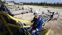 An oil field worker walks up stairs near wellheads that inject steam into the ground and pump oil out at the Cenovus Energy Christina Lake Steam-Assisted Gravity Drainage project in Alberta. (Todd Korol/Reuters)