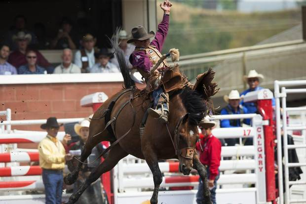 Cody DeMoss rides Southern Star in the saddle bronc event during the rodeo at the Calgary Stampede.