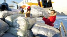 A Red Cross worker unloads sleeping bags at the airport in Attawapiskat, Ont., on Nov. 29, 2011. (Adrian Wyld/THE CANADIAN PRESS)