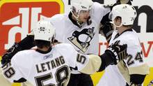 Pittsburgh Penguins captain Sidney Crosby,c entre, celebrates his goal Sunday with teammates Kris Letang, left, and Matt Cooke during the second period of Game 3 of their NHL Eastern Conference quarter-final against the Ottawa Senators. (BLAIR GABLE)