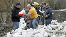 Volunteers sandbag a dike along the Assiniboine River in Brandon, Man., on April 9, 2011. (John Woods/The Canadian Press/John Woods/The Canadian Press)