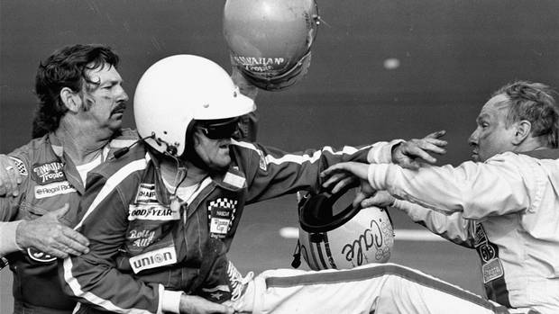 5 FILE - In this Feb. 18, 1979, file photo, Bobby Allison holds race driver Cale Yarborough's foot after Yarborough, right, kicked him following an argument when Yarborough stopped his car during the final lap of the Daytona 500, in Daytona Beach, Fla. The brawl in the closing moments of the first race to be broadcast live in its entirety was a monumental moment for NASCAR, and the lasting image as the traditionally Southern sport officially announced its arrival on the national scene. (AP Photo/Ric Feld, File)