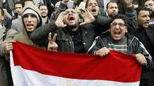 Egyptian demonstrators hold their national flag during demonstration in Cairo on Jan. 27, 2011 demanding the ouster of President Hosni Mubarak. (AFP/Getty Images)