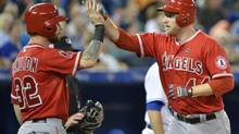 Los Angeles Angels first baseman Mike Trumbo, right, celebrates his two run home run with teammate Josh Hamilton, left, during second inning AL baseball action in Toronto on Wednesday, Sept. 11, 2013. (Nathan Denette/THE CANADIAN PRESS)