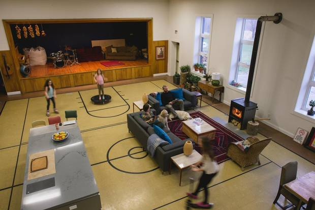 Alysa Hawkins and Jesse Parker with their three daughters in the 1960s school they converted in to their new home. The school gym serves as the living room, kitchen and dinning room, it also makes the perfect playground for their daughters Reya, Wini and Ruby. The flooring is very durable and perfect for roller blading and scootering.