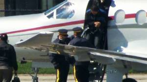 RCMP escort a bomb plot suspect off a plane in Toronto on April 22, 2013.