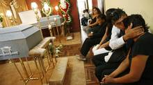 Monica Correa, right, wife of migrant worker Jose Valdiviezo and mother of Fernando Valdiviezo, is comforted by a relative during their funeral at her home in Lima on Feb. 21, 2012. A crash between a flatbed truck and a van carrying migrant farm workers on a rural crossroads in southwestern Ontario on Feb. 6 killed 10 migrant workers from Peru, including Jose and Fernando, as well as a Canadian citizen, according to media reports. (ENRIQUE CASTRO-MENDIVIL/REUTERS)