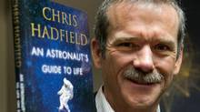 """Retired Canadian astronaut Chris Hadfield holds a copy of his new book """"an Astronaut's Guide to Life on Earth"""" while on a media tour Wednesday, November 27, 2013 in Montreal. (Ryan Remiorz/THE CANADIAN PRESS)"""