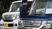 A man inspects Honda vehicles displayed in front of Honda Motor Co. headquarters in Tokyo Monday, Oct. 29, 2012. (Koji Sasahara/AP)
