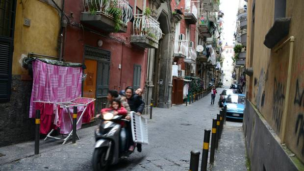 People ride a scooter through a Naples alleyway.