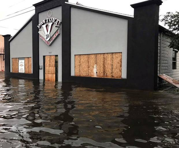 Daytona Beach, Fla., Sept. 11: A boarded-up motorcycle shop stands in flood waters.