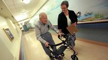 Ministry of Healthy Living and Sport's, Dr. Vicky Scott, walks with Broadmead Care Society resident Gene Seward through a hallway wearing his track pants with a built in hip protector. A soft padded energy absorbent padding worn to prevent hip fractures. (Chad Hipolito For The Globe And Mail/Chad Hipolito For The Globe And Mail)
