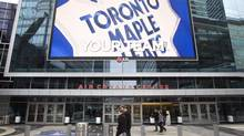In this file photo pedestrians walk past the Air Canada Centre as a screen projects an image of the Toronto Maple Leafs logo in Toronto. (Darren Calabrese/THE CANADIAN PRESS)