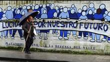 "A man walks past graffiti that reads ""Fight for our future"" in Turon, northern Spain (ELOY ALONSO)"