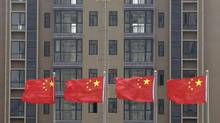 Chinese national flags fly in front of a newly built residential apartment in Wuhan, Hubei province, July 10, 2012. (DARLEY SHEN/Reuters)