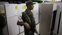 A member of the National Guard stands guard during a inspection of prices at a store in La Guaira outside Caracas (JORGE SILVA)