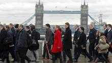 Rush-hour workers pass the Tower Bridge in the financial district of the City of London. Britain's large financial institutions are planning to reduce their property requirements during the next two years as the sector sheds jobs. (Luke MacGregor/Reuters)