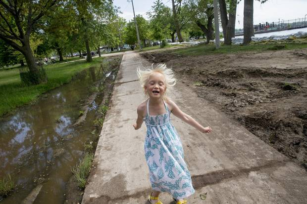 Billie Page walks near large puddles of water and a shoreline lined with sand bags on Ward's Island.